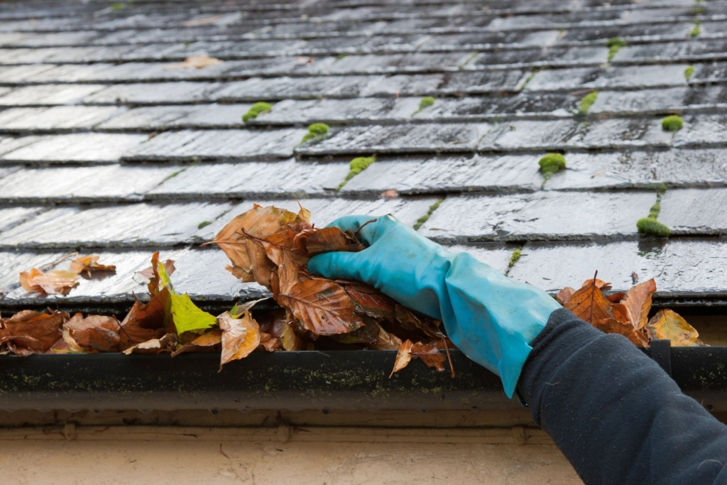 A hand cleaning leaves from a gutter