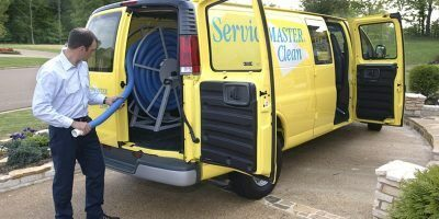 Man Pulling Hose out of a ServiceMaster Van